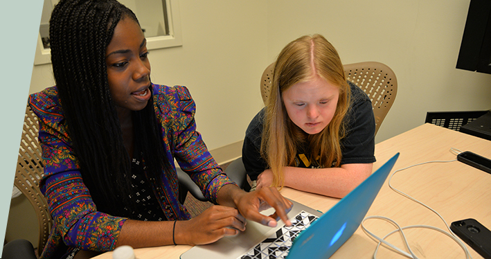 Education coach Camille Spencer, a senior environmental studies major, helps ACE-IT participant Sarah Lancaster study and work on astronomy homework.
