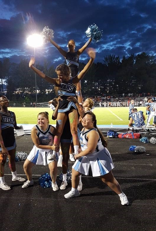 Cheerleaders at a night time football game forming a pyramid.