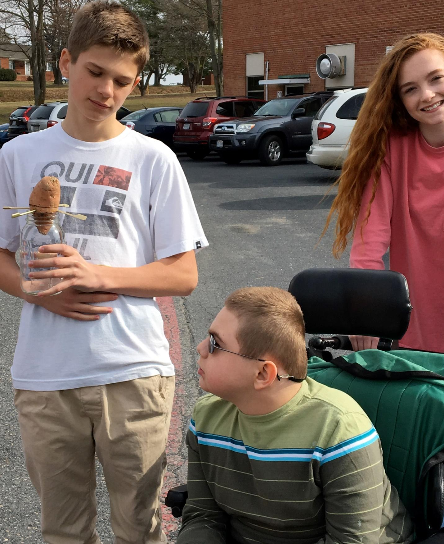 Three students in a parking lot holding a potato experiment.