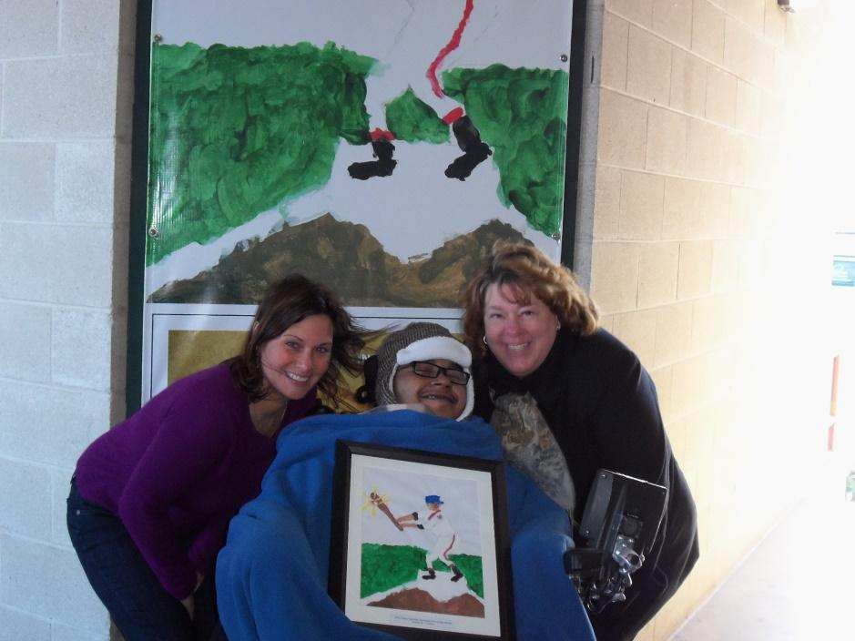 Jerziah with his teachers in front of one of his paintings.